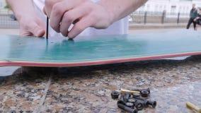 Junge Kerldurchschlagslöcher in einem Skateboard stock video