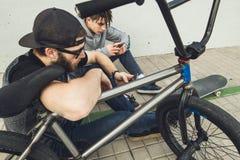 Junge Kerle, die das Mobile auf der Straße aufpassen Moderner Lebensstil von jungen Leuten stockfotos