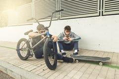 Junge Kerle, die das Mobile auf der Straße aufpassen Moderner Lebensstil von jungen Leuten stockfoto