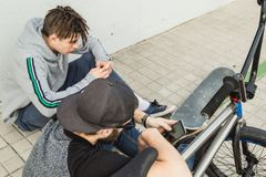 Junge Kerle, die das Mobile auf der Straße aufpassen Moderner Lebensstil von jungen Leuten lizenzfreies stockbild