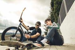 Junge Kerle, die das Mobile auf der Straße aufpassen Moderner Lebensstil von jungen Leuten lizenzfreie stockbilder