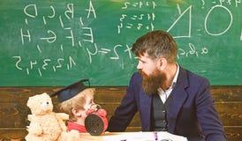 Junge, Kind in der graduierten Kappe betrachtet Gekritzel auf Tafel, w?hrend Lehrer erkl?rt Lehrer mit Bart, Vater unterrichtet lizenzfreie stockbilder