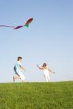 Junge Kinder laufen gelassen mit Drachen Stockfotos