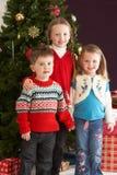 Junge Kinder mit Geschenken vor Baum Stockfotos