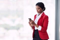 Junge kleideten formal die Afroamerikanerfrau, die unter Verwendung ihres Telefons beschäftigt ist Stockfotos