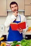 Junge kochen mit dem Kochbuch, das an Rezept denkt Lizenzfreie Stockfotografie