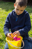 Junge kontrolliert seine Ostereier nach einer Jagd Lizenzfreie Stockfotografie