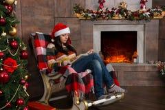 Junge konzentrierten Frau in der lustigen Weihnachtshutlesung während Si Stockfotos