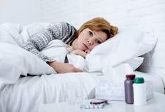 Junge kranke Frau, die auf dem schlechten Schauen des kranken Gefühls des Betts selbst fieberhaftes und schwaches leidendes Winte stockbilder