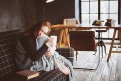 Junge kranke Frau, die zu Hause mit heißem Getränk auf gemütlicher Couch heilt stockfotografie