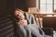Junge kranke Frau, die zu Hause mit heißem Getränk auf gemütlicher Couch heilt lizenzfreie stockbilder