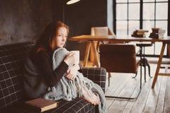 Junge kranke Frau, die zu Hause mit heißem Getränk auf gemütlicher Couch heilt stockbild