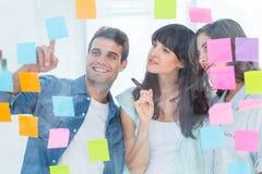 Junge kreative Geschäftsleute, die Bildeditor betrachten Stockbilder