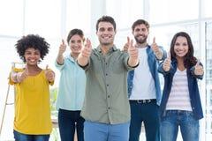 Junge kreative Geschäftsleute, die oben Daumen gestikulieren Stockfoto
