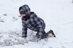 Junge kriecht in den Schnee Stockfotografie