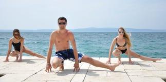 Junge Kursteilnehmer, die Yoga üben Stockbild