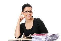 Junge Kursteilnehmerfrau, die am Schreibtisch erlernt lizenzfreie stockbilder