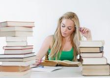 Junge Kursteilnehmerfrau mit Lots Büchern Stockbild