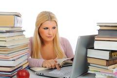 Junge Kursteilnehmerfrau mit Lots der Bücher und des Laptops Stockfoto