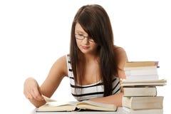 Junge Kursteilnehmerfrau mit Lots studing Büchern. Lizenzfreie Stockbilder