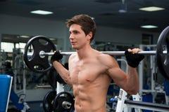 Junge lächelnde anhebende Gewichte des Athleten in der Turnhalle Stockbild