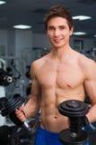 Junge lächelnde anhebende Gewichte des Athleten in der Turnhalle Stockfoto