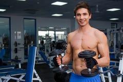 Junge lächelnde anhebende Gewichte des Athleten in der Turnhalle Stockfotos