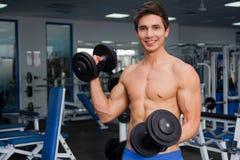 Junge lächelnde anhebende Gewichte des Athleten in der Turnhalle Stockfotografie
