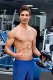 Junge lächelnde anhebende Gewichte des Athleten in der Turnhalle Lizenzfreies Stockfoto