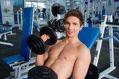 Junge lächelnde anhebende Gewichte des Athleten in der Turnhalle Stockbilder