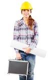 Junge lächelnde Arbeitskraft im Sturzhelm mit einem Diplomaten Lizenzfreies Stockfoto