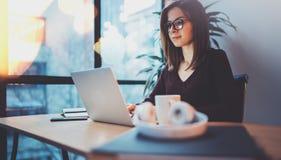 Junge lächelnde Augen-Glasfunktion des Mädchens tragende auf Laptop an ihrem Arbeitsplatz im Nachtbüro horizontal Unscharfer Hint stockfotos
