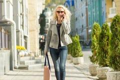 Junge lächelnde Blondine, die auf eine Stadtstraße, sonniger Tag des Herbstes, goldene Stunde gehen stockbilder