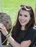 Junge lächelnde Dame, die auf eine Couch hält Lizenzfreies Stockfoto
