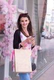 Junge lächelnde Dame mit dem Einkaufen in der Hand ist auf der Straße wert stockbilder