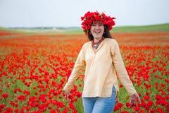 Junge lächelnde Frau auf dem Mohnblumegebiet lizenzfreie stockfotos