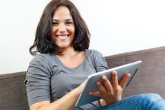 Junge lächelnde Frau bei der Anwendung der Berührungsfläche Lizenzfreie Stockfotos