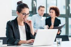 Junge lächelnde Frau bei der Anwendung eines Laptops im Büro Lizenzfreie Stockbilder