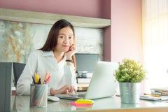 Junge lächelnde Frau beim Büro zu Hause bearbeiten Lizenzfreies Stockfoto