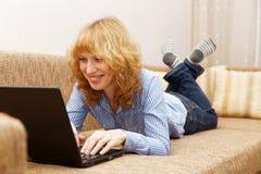Junge lächelnde Frau benutzt einen Laptop Stockfotografie