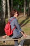 Junge lächelnde Frau, die auf dem Zaun halb-gedreht sitzt Lizenzfreie Stockfotos
