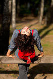 Junge lächelnde Frau, die auf dem Zaun sitzt Stockbilder