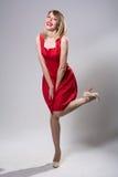 Junge lächelnde Frau, die auf einem Bein in einem roten Kleid steht Stockbild
