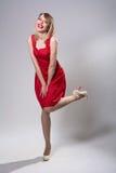 Junge lächelnde Frau, die auf einem Bein in einem roten Kleid steht Lizenzfreie Stockfotografie