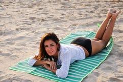 Junge lächelnde Frau, die auf Tuch am Strand legt Lizenzfreies Stockbild