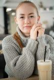 Junge lächelnde Frau, die bei Tisch im Café lächelt mit den Händen auf ihrem Mund sitzt Hippie-Ingwer, Gegähne, seinen Mund bedec stockfotos