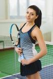 Junge lächelnde Frau, die das Tennis und Aufstellung Innen spielt Stockfoto