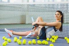 Junge lächelnde Frau, die das Tennis und Aufstellung Innen spielt Stockfotografie