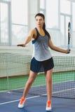 Junge lächelnde Frau, die das Tennis und Aufstellung Innen spielt Lizenzfreie Stockfotos