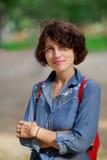 Junge lächelnde Frau, die die Kamera untersucht Stockfotografie